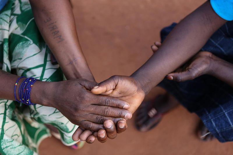 Entinen lapsisotilas pitää äitiään kädestä kiinni.